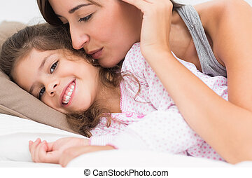Mother kissing daughter on the cheek in bed