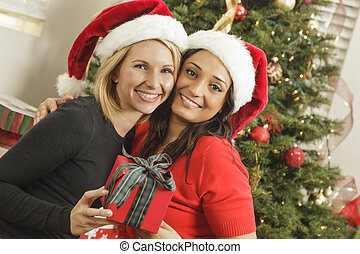 Young Mixed Race Girlfriends with Christmas Gift -...