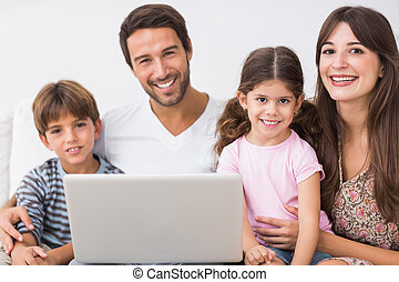 Happy family with laptop on the couch