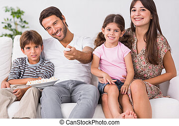 Happy family watching television together in the living room