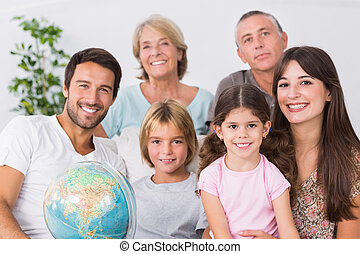 Cheerful family sitting on couch with a globe