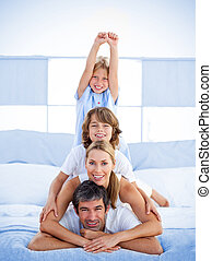 Jolly happy family having fun in the bedroom