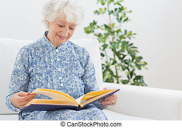Elderly smiling woman looking at photos on a sofa