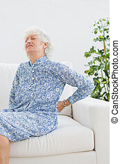 Elderly woman with back pain in the living room