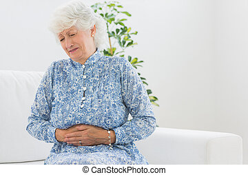 Elderly woman having a belly pain in the living room