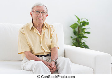Elderly man looking at camera in the sofa
