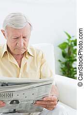 Elderly focused man reading newspapers on a sofa