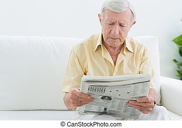 Elderly concentrated man reading newspapers on a sofa