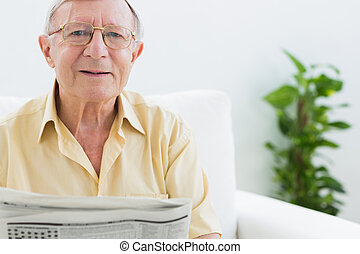 Cheerful elderly man reading the news in the living room