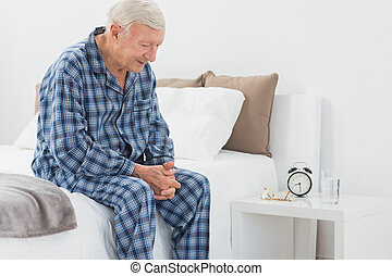Elderly man sitting on the bed in the bedroom