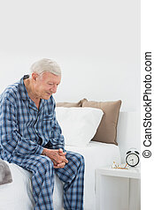 Calm elderly man sitting on the bed in the bedroom