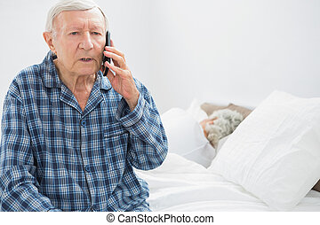 Old man on the phone sitting on the bed