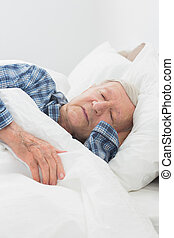 Elderly man sleeping on the bed