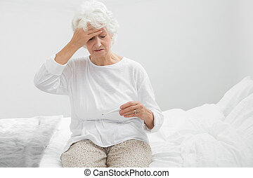 Aged woman suffering with fever in the bedroom