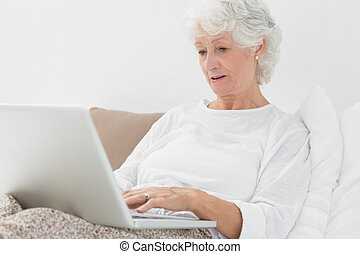 Old woman typing on her laptop lying on her bed