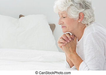 Old woman praying before going to bed