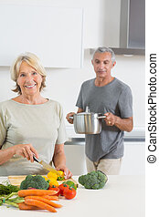 Husband bringing a pan to his smiling wife in the kitchen