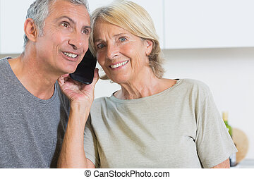 Cheerful mature couple listening a call together in the...