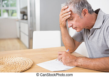Focused man reading documents at home