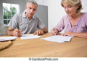 Couple signing documents together in the kitchen