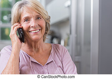 Happy mature woman calling in the kitchen