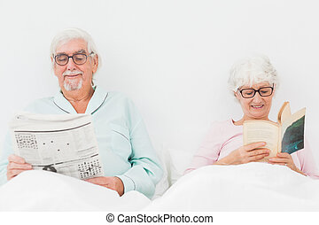 Happy couple reading in bed - Happy elderly couple reading...