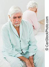 Elderly couple not speaking to each other in bedroom