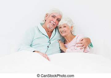 Smiling couple in bed