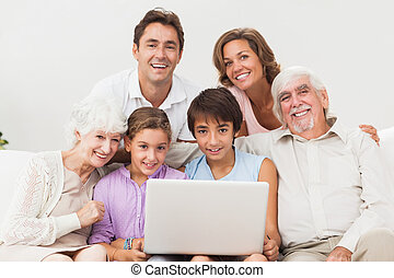 Multi-generation family on couch with laptop