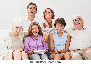 Multi-generation family on couch watching tv - Multi...