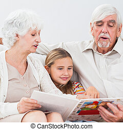 Little girl reading with grandparents