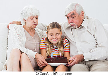 Little girl and grandparents blowing out the candles on...