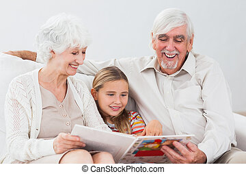 Happy little girl reading with grandparents