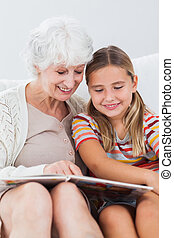 Little girl reading with granny - Little girl sitting on...