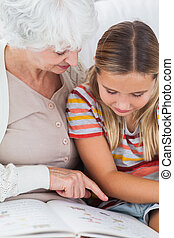 Girl reading with granny - Girl reading book with granny on...