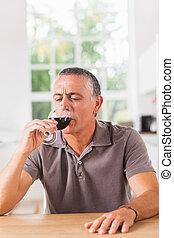Man drinking glass of red wine