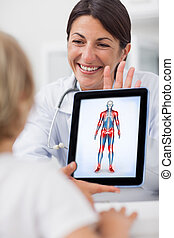 Smiling doctor showing a tablet computer to a child in...
