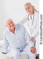 Smiling doctor helping man to sit up - Smiling doctor...