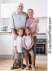 Children standing with grandparents in kitchen