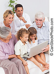 Extended family watching laptop on the couch together