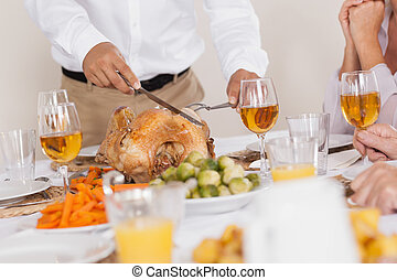 Turkey being carved at celebratory holiday dinner