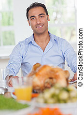 Man sitting at head of dinner table at thanksgiving