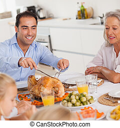 Man carving the thanksgiving turkey at head of table