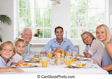 Family smiling at thanksgiving - Family smiling around the...