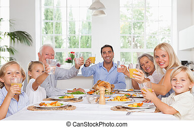 Happy family toasting at thanksgiving dinner - Happy family...