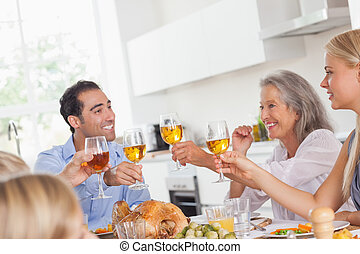 Family raising their glasses at thanksgiving dinner - Happy...