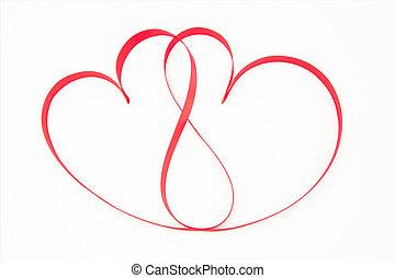 Pink ribbon shaped into intertwining hearts on white...
