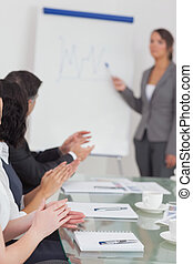 Businesswoman explaining and her colleagues clapping