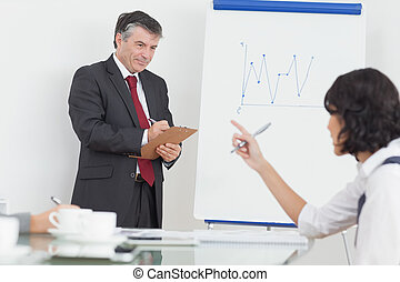 Businessman writing on clipboard in office - Businessman...