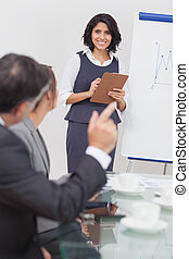 Man posing a question to his businesswoman with clipboard in...